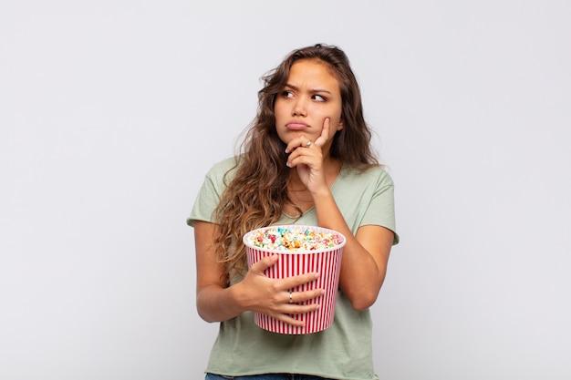 Молодая женщина с поп-консервом думает, сомневается и сбивается с толку, с разными вариантами, задается вопросом, какое решение принять