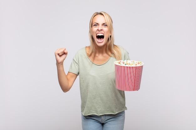 Молодая женщина с ведром для кукурузы агрессивно кричит с сердитым выражением лица или со сжатыми кулаками, празднуя успех