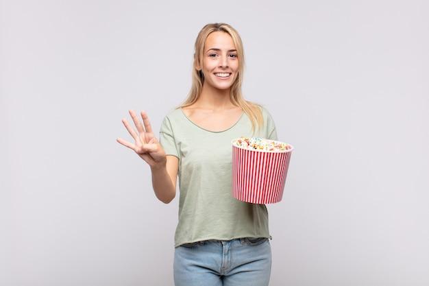 ポップコーンのバケツを持った若い女性が笑顔でフレンドリーに見え、手を前に向けて4番または4番を示し、カウントダウン