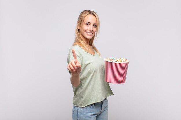 Молодая женщина с ведром для кукурузы гордо и уверенно улыбается, триумфально принимая позу номер один, чувствуя себя лидером
