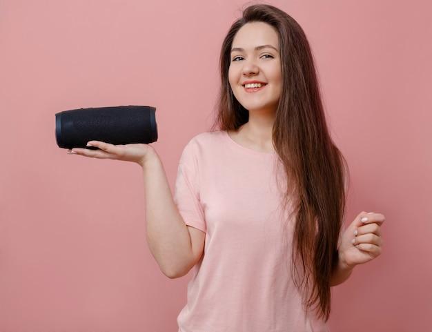 ピンクの背景にポータブルスピーカーを手に若い女性