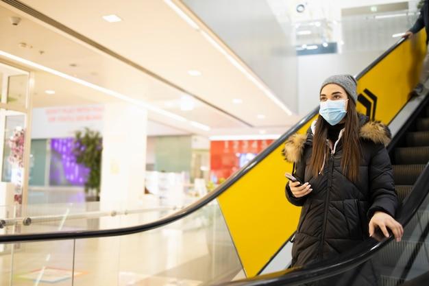 쇼핑몰에서 계단을 복용 보호 마스크와 젊은 여자