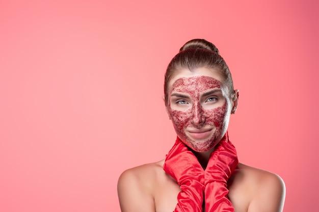 ピンクでポーズをとって赤い手袋で彼女の顔に赤い化粧品のマスクを持つ若い女性