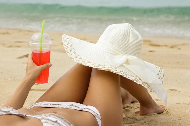 Молодая женщина с красным освежающим напитком на пляже