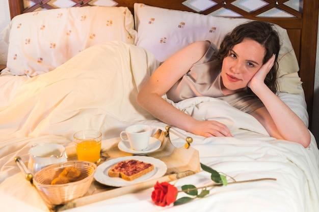 Молодая женщина с романтическим завтраком с апельсиновым соком, кофейными тостами, кексами и розой