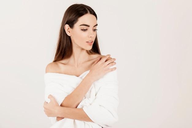 美しさの治療の後に魅力的なポーズを持つ若い女性