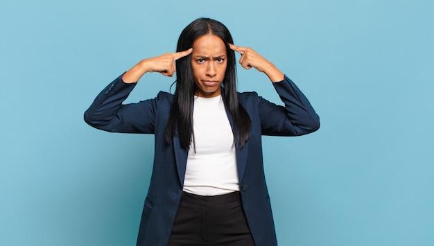 真剣で集中した表情の若い女性、ブレーンストーミングを行い、難しい問題について考える