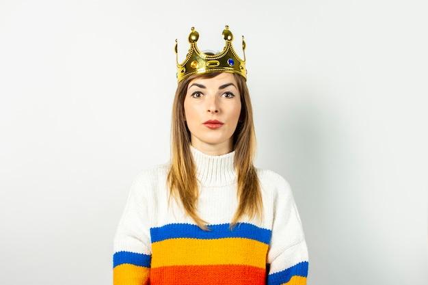 Молодая женщина с серьезным лицом в короне и свитере на белом фоне