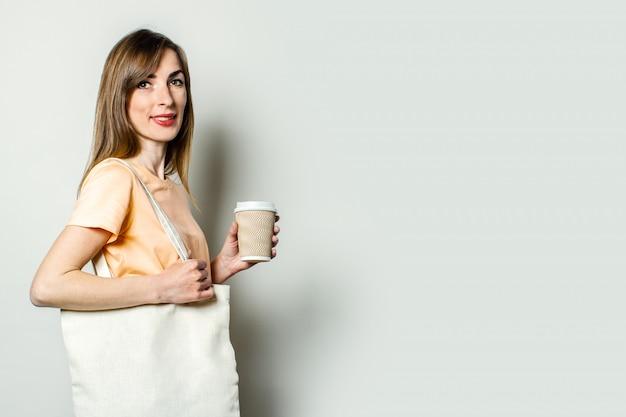 ショッピングバッグを持つ若い女性と明るい背景にコーヒーと紙コップを保持