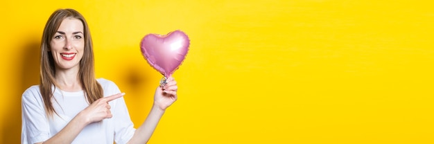 笑顔の若い女性は、ハート型の風船を手に持って、黄色の背景に指を向けます。バナー。