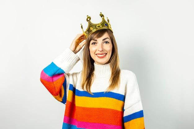 Молодая женщина с улыбкой в короне и свитере смеется на белом фоне