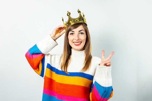 Молодая женщина с улыбкой в короне и свитере смеется