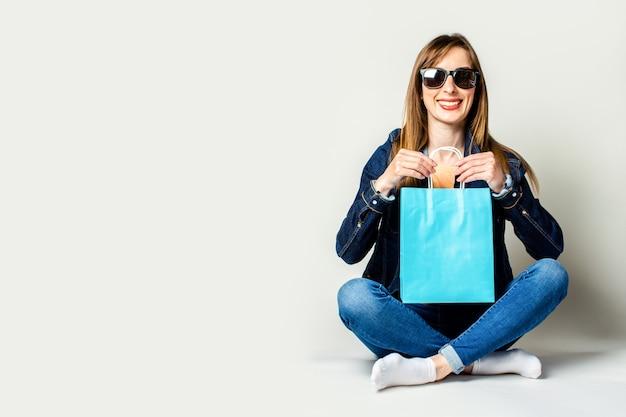 デニムジャケットとサングラスで笑顔の若い女性は、明るい空間の床に座って買い物袋を保持しています。バナー
