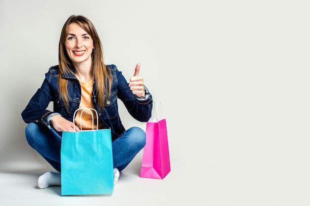 デニムジャケットで笑顔の若い女性は、明るい空間の床に座っている間買い物袋を保持し、ジェスチャーをします。