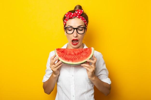 Молодая женщина с улыбкой в красной повязке на голову и в очках ест арбуз на желтой стене.