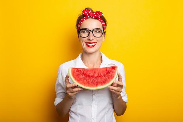 Молодая женщина с улыбкой в красной повязке и очках держит арбуз на желтой стене.
