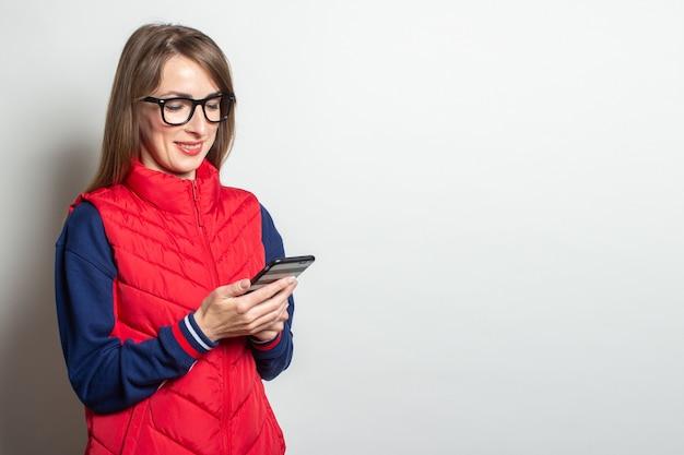 赤いベストを着た笑顔の若い女性が明るい壁に向かって彼女の電話をのぞき込む