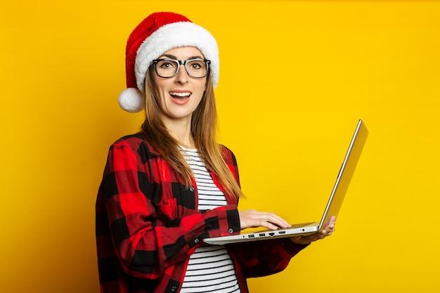 Молодая женщина с улыбкой в шляпе санта-клауса и красной рубашке в клетке держит ноутбук