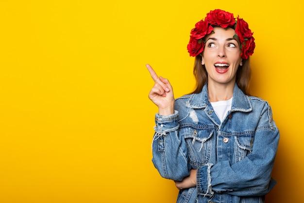 笑顔の若い女性は、デニムのジャケットと黄色い壁の頭に赤い花の花輪を着て横を向いています。