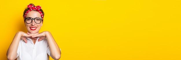 黄色の壁に彼女の頭に眼鏡と赤いヘッドバンドを身に着けている笑顔の若い女性。