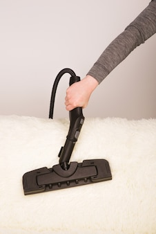 스팀 청소기와 젊은 여자는 소파에 카펫을 청소