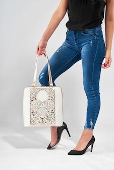 Молодая женщина с потрясающими ногами носит модную белую сумку с тиснением и ручками. также она носит синие джинсы, черный топ и туфли на высоких каблуках. фотография сделана на белом студийном фоне.