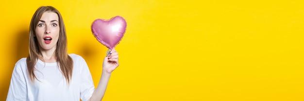 驚いた顔の若い女性は、黄色の背景にハート型の風船を手に持っています。バナー。