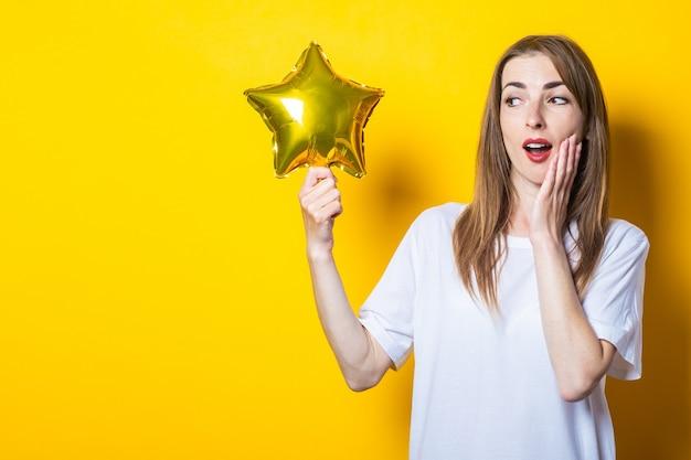 Молодая женщина с удивленным лицом держит в руках звездный шар на желтом фоне. баннер.