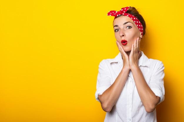 Молодая женщина с удивленным лицом держит руки на подбородке, в очках и повязке на голове на желтой стене. баннер.