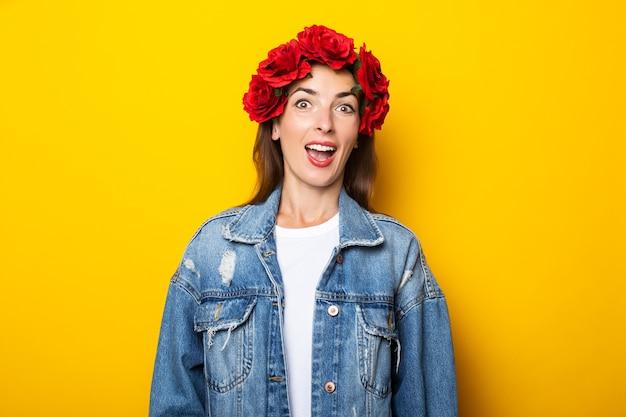 デニムジャケットに驚いた顔と黄色の壁に頭に赤い花の花輪を持つ若い女性。