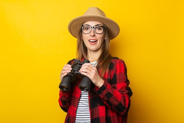 帽子と黄色の背景に双眼鏡を手に持っている格子縞のシャツで驚いた顔を持つ若い女性。