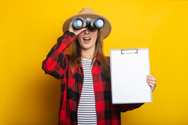 帽子と格子縞のシャツで驚いた顔を持つ若い女性はクリップボードを保持し、黄色の背景に双眼鏡を通して見ています。