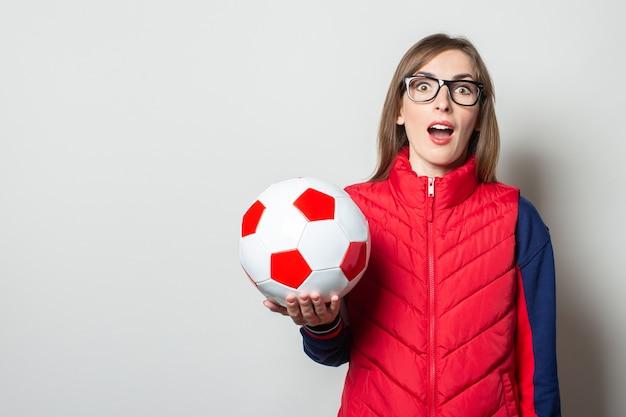 Молодая женщина с удивленным лицом в красном жилете держит в руках футбольный мяч