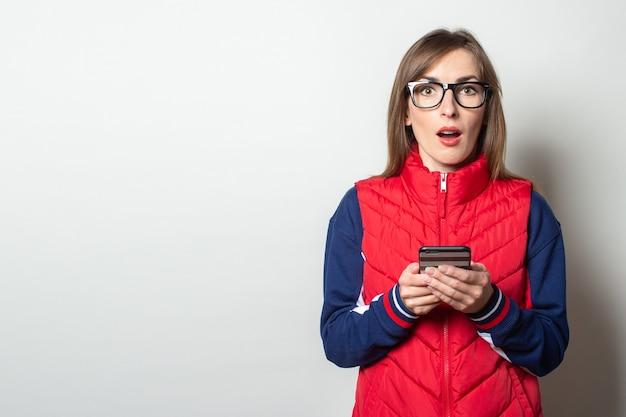赤いベストに驚いた顔をした若い女性は、明るい壁に彼女の手で彼女の電話を保持します
