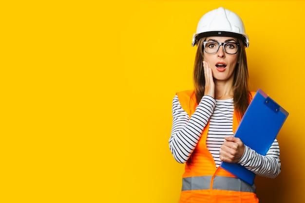 조끼와 하드 모자에 놀란 얼굴을 가진 젊은 여자는 노란색에 클립 보드를 보유