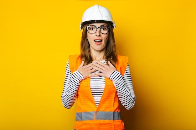 黄色の背景にベストとヘルメットの驚きの顔を持つ若い女性。建設コンセプト、新しい建物。バナー。