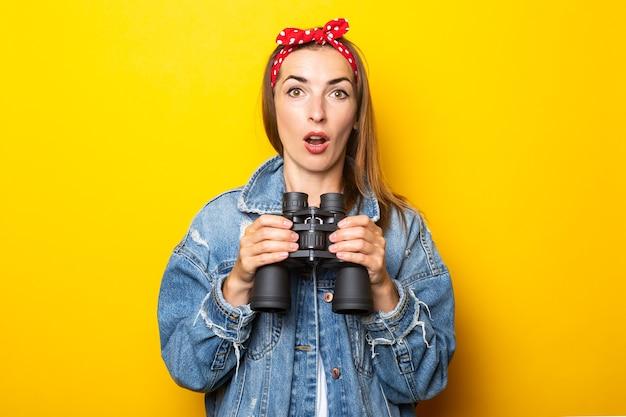 Молодая женщина с удивленным лицом в джинсах и плотом на голове держит в руках бинокль на желтой стене. баннер.