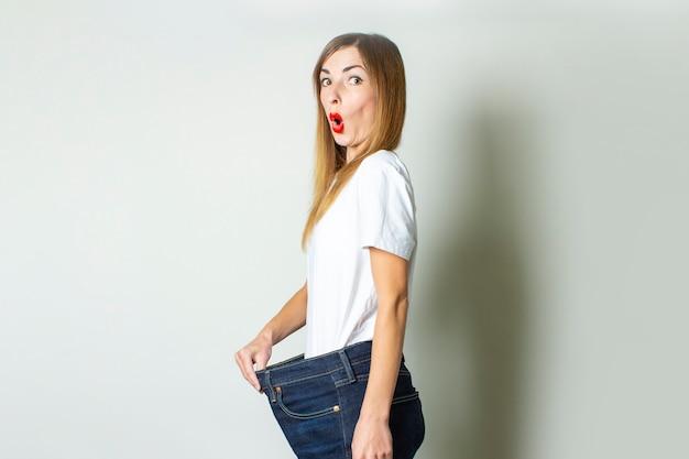 Молодая женщина с удивленным лицом в огромных джинсах на светлом фоне