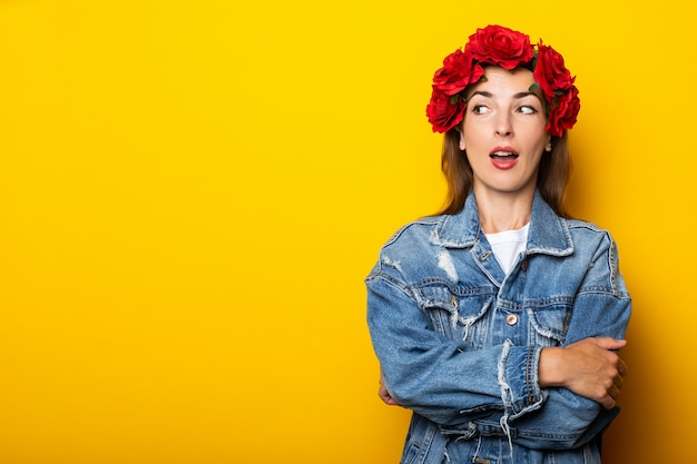 驚いた顔をした若い女性は、デニムのジャケットと黄色い壁の頭に赤い花の花輪を着て横を向いています。