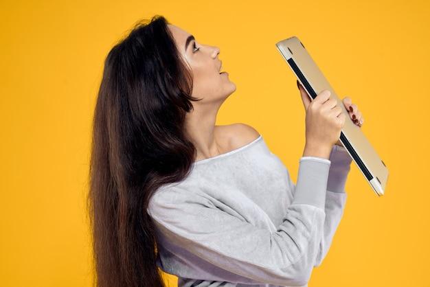 Молодая женщина с планшета, ноутбука и наушников позирует на стене, разные эмоции