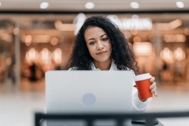 Молодая женщина с кофе на вынос работает на своем ноутбуке