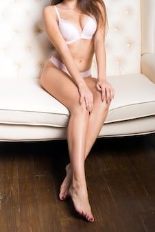 引き締まった美しい体と長い脚を持つ若い女性がスタジオのソファに座っています