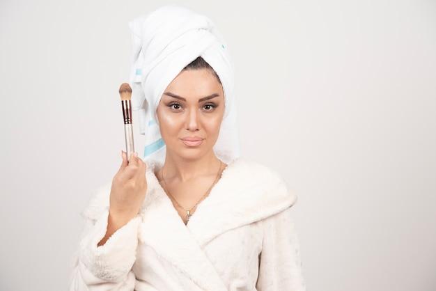 彼女の頭にタオルとタッセルを持つ若い女性