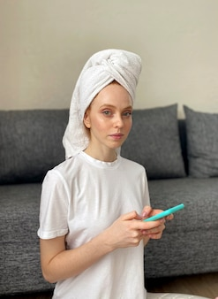 スキンケアルーチンをしている彼女の頭にタオルを持つ若い女性