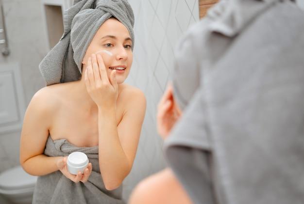 거울 앞에서 머리에 수건을 두른 젊은 여성은 주름과 노년으로 볼에 크림을 바르고 있습니다. 피부 관리의 개념입니다.