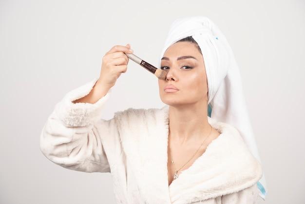頭にタオルを持った若い女性がタッセルで鼻をくすぐる