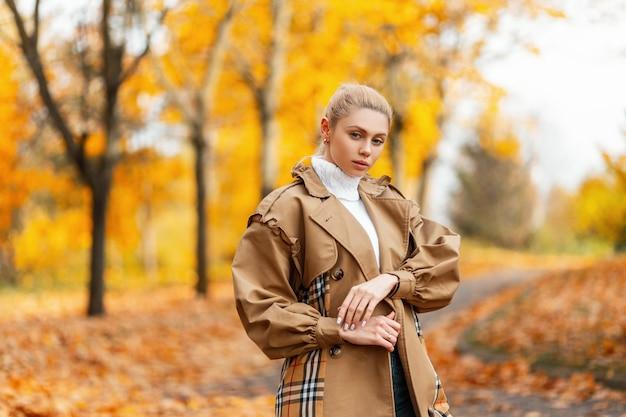 エレガントなコートを着たトレンディな髪型の若い女性が公園で屋外でポーズをとる