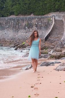 ビーチを歩いているターコイズブルーのドレスを着た若い女性