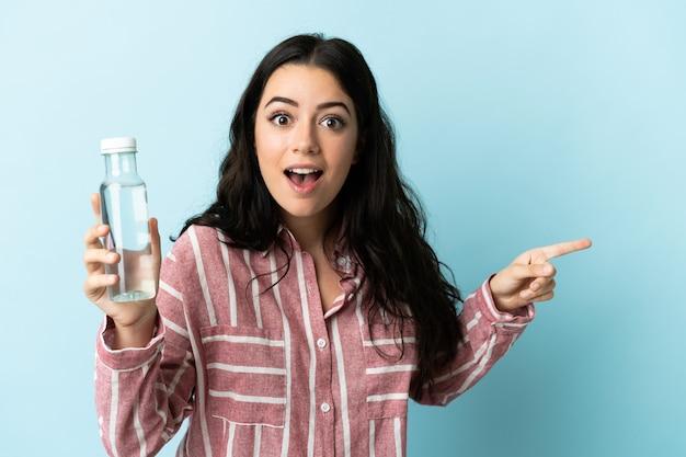 青い背景に分離された水を持つ若い女性は驚いて、人差し指を横に向ける