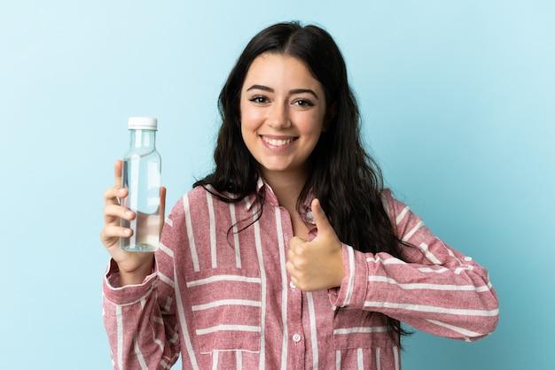 Молодая женщина с водой, изолированной на синем, с большими пальцами руки вверх, потому что произошло что-то хорошее